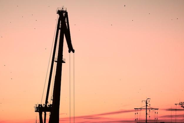 Silhouet van containerkraan op zonsondergang