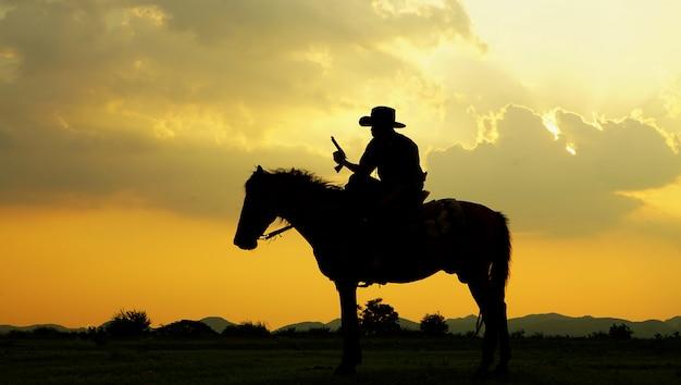 Silhouet van cowboy het berijden paard tegen zonsondergang op het gebied