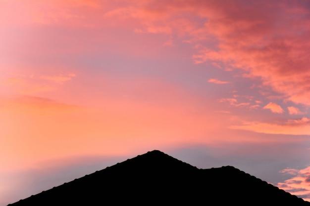 Silhouet van dak op een nieuw huis met roze fantasiehemel vóór zonsondergang