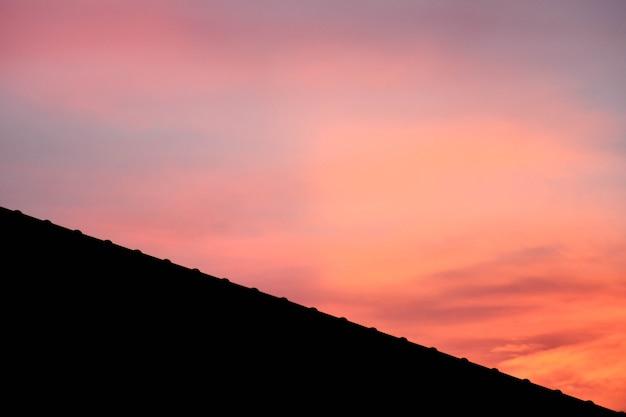 Silhouet van dak op een nieuw huis met roze fantasiehemel vóór zonsondergangachtergrond