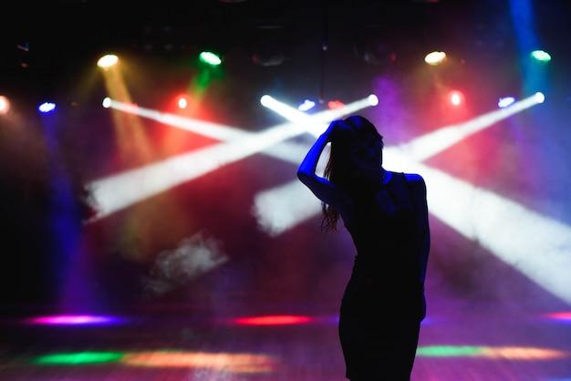 Silhouet van dansend meisje tegen discolichten
