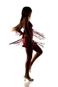 Silhouet van dansende slanke mooie vrouw in sexy rode jurk en hoge hakken schoenen geïsoleerd over wit