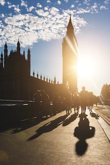 Silhouet van de big ben en toeristen in londen bij zonsondergang