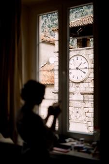 Silhouet van de bruid die voor de huwelijksceremonie bij het raam in een hotelkamer staat