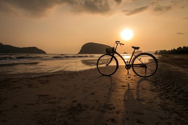 Silhouet van de fiets op het strand, fietsen op strand zonsondergang of zonsopgang