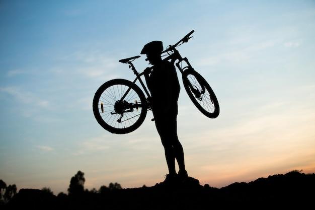 Silhouet van de fietser die een racefiets berijdt bij zonsondergang