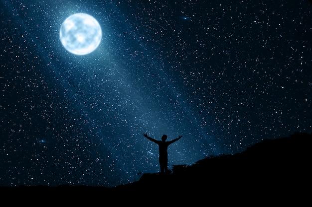 Silhouet van de gelukkige mens die van de nacht met maan en sterren geniet