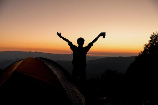 Silhouet van de gelukkige mens met het houden van de kop van de koffiekop dichtbij tent rond bergen