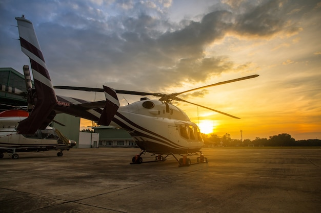 Silhouet van de helikopter op het parkeerterrein of de baan met sunrise achtergrond