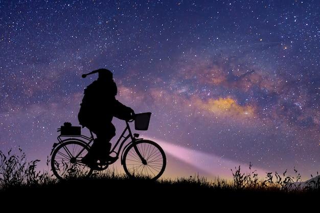 Silhouet van de kerstman die op zijn fiets rijdt om een geschenk te dragen onder de achtergrond van de melkweg.