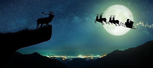 Silhouet van de kerstman die 's nachts op hun rendieren vliegt over de volle maan