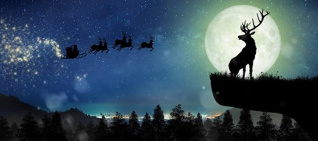 Silhouet van de kerstman die 's nachts op rendieren over volle maan vliegt