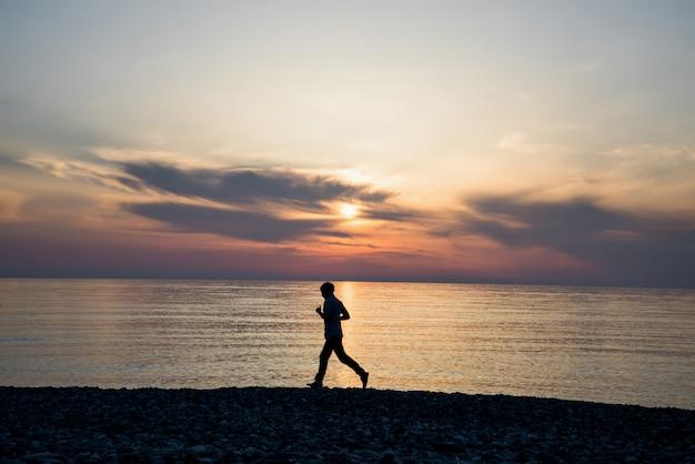 Silhouet van de lange sport actieve mens die en op strand in busch onder zonsondergang lopen uitoefenen.