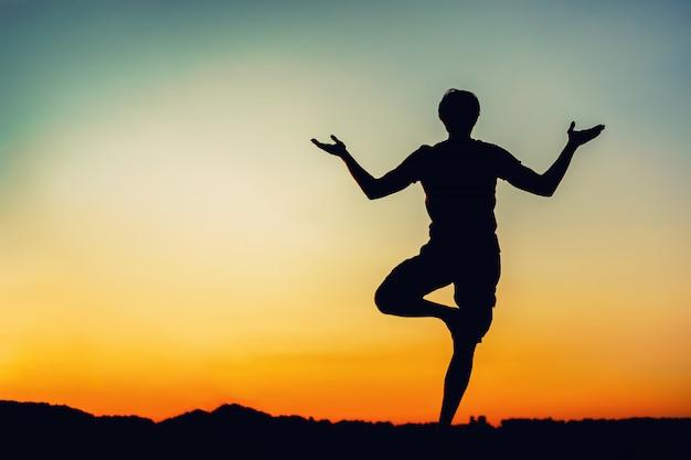 Silhouet van de man in yoga vormen bij zonsondergang