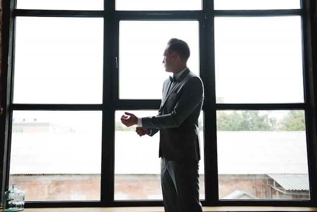Silhouet van de man voor het raam. ochtend van de bruidegom. kamer in loftstijl. grote ramen.