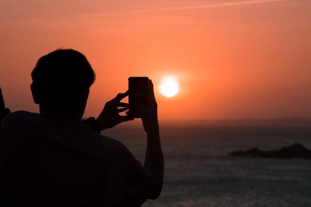 Silhouet van de mens die foto van zonsondergang neemt