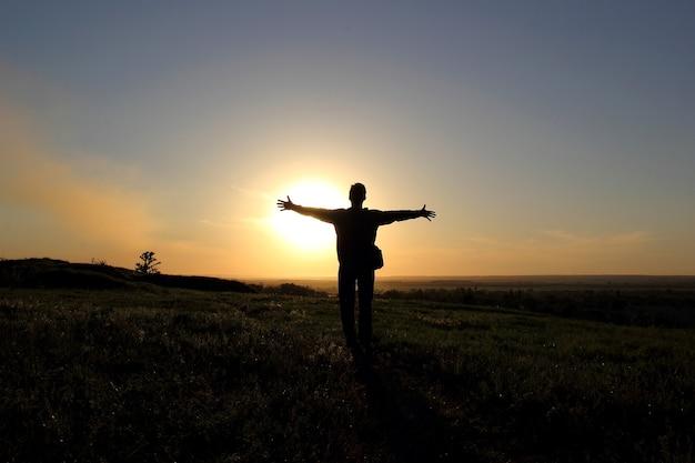 Silhouet van de mens in een veld bij zonsondergang