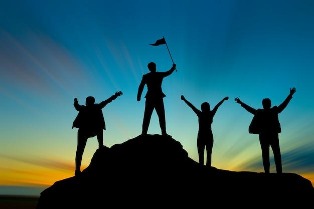 Silhouet van de mens op bergbovenkant over hemel en zon licht succes, leiderschap en mensenconcept