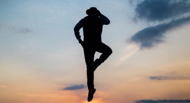 Silhouet van de mens springt of vliegt op zonsopganghemel terwijl hij telefoneert, communicatie