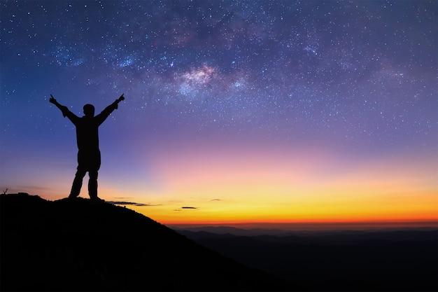 Silhouet van de mens staat op de top van de berg en het verspreiden van de hand