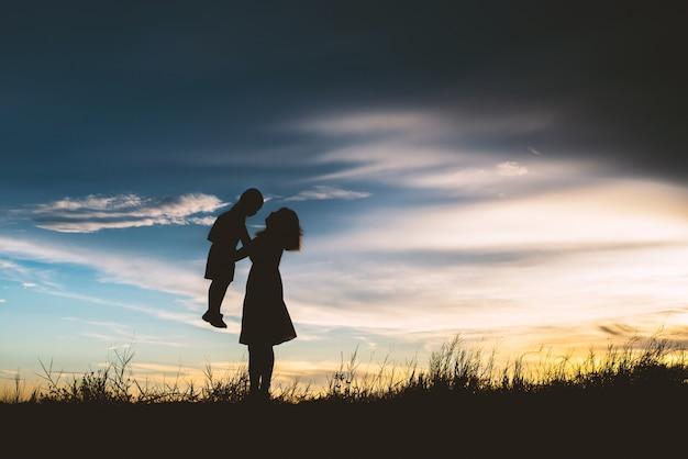 Silhouet van de moeder speelt met haar zoon in de wei