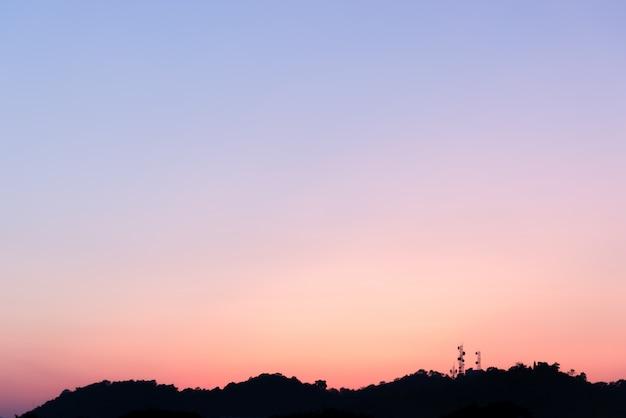 Silhouet van de telecommunicatietoren op de berg met kleurrijke hemel.