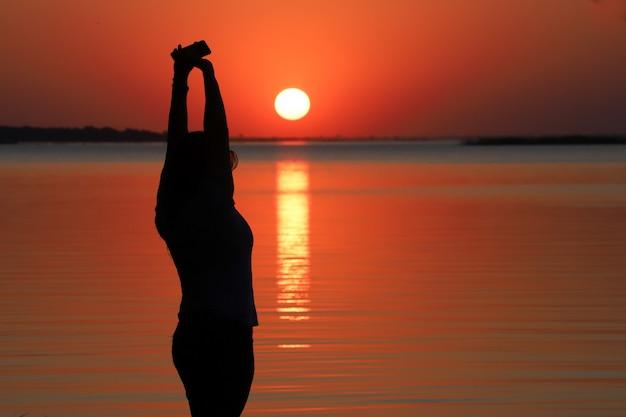 Silhouet van de vrouw bij zonsondergang met de zon ondergaat over de wateren van een rivier