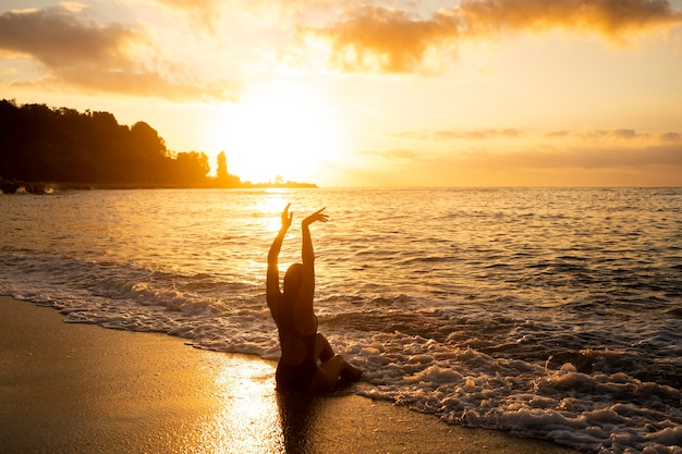 Silhouet van de vrouw die zich voordeed aan het strand