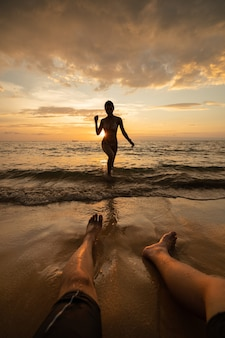 Silhouet van de vrouw op het strand bij zonsondergang met man benen