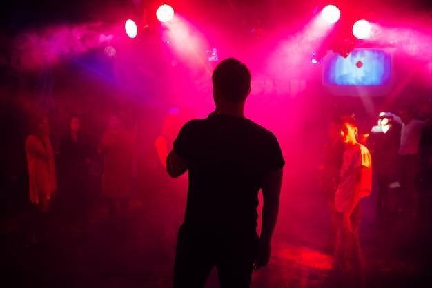 Silhouet van de zanger tegen een menigte van mensen op een feestje in een nachtclub