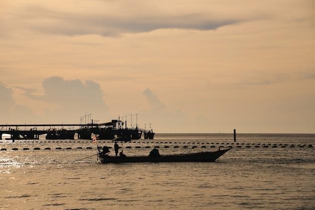 Silhouet van de zee en boot in de zonsondergang