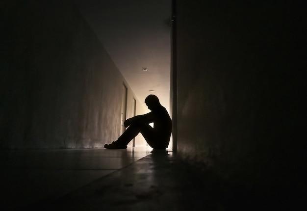 Silhouet van depressieve man zit op loopbrug van woningbouw sad lonely unhappy concept