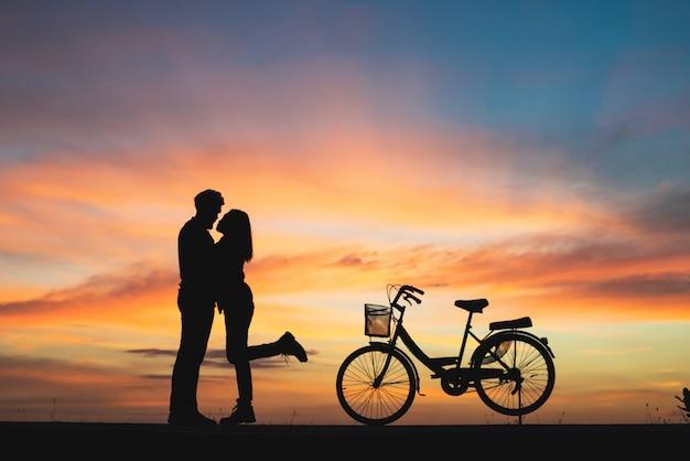 Silhouet van echtpaar in liefde kussen in zonsondergang. paar in liefde concept.