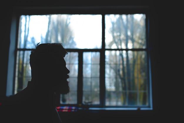 Silhouet van een bebaarde man op een achtergrond van venster