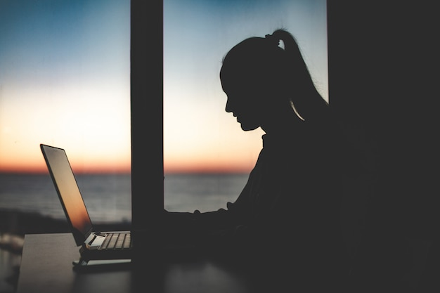 Silhouet van een bedrijfsvrouw die laat bij laptop tegen het venster bij zonsondergang werkt. nacht en avond online werken