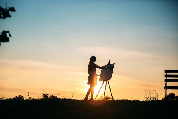 Silhouet van een blonde meisje kunstenaar schildert een schilderij op het doek