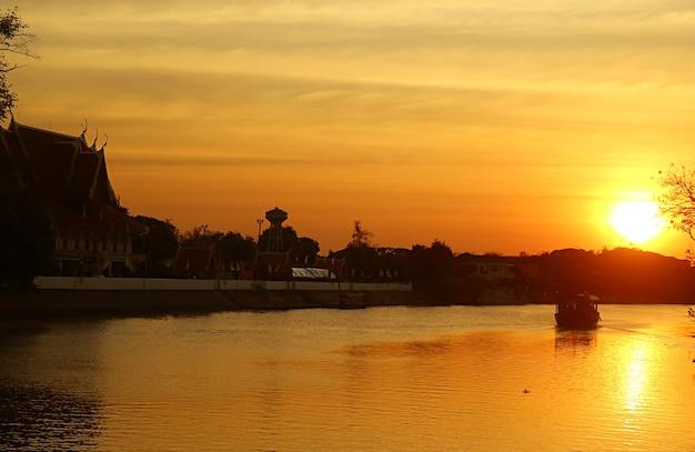 Silhouet van een boeddhistische tempel op de oever van de chao phraya-rivier in golden sunset view