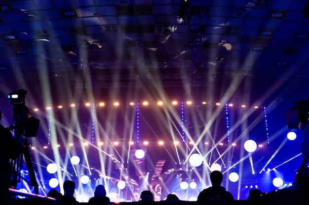 Silhouet van een concertmenigte. het publiek kijkt naar het podium. feestmensen bij een rockconcert. muzikaal feest. muzikale voorstelling. groep silhouet. jong publiek.