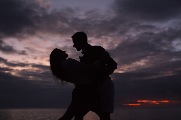 Silhouet van een dansend paar bij zonsondergang
