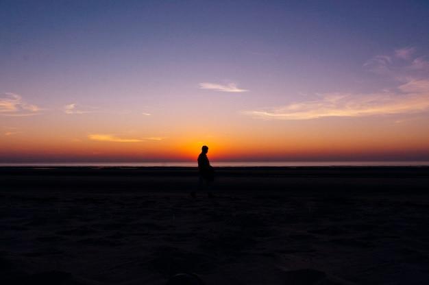 Silhouet van een eenzame persoon die op het strand loopt met het prachtige uitzicht op de zonsondergang op de achtergrond