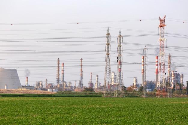 Silhouet van een elektrisch onderstation, energie en industrie en groen veld. industriële hoogspanningsomvormer metalen structuur en hoogspanningsleidingen.