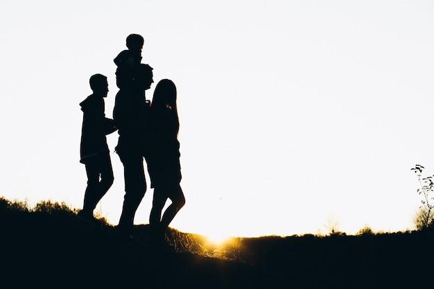 Silhouet van een familie die tegen de zonsondergangtijd loopt