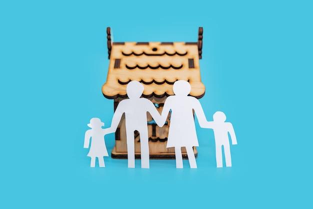 Silhouet van een familie en een houten huis op een blauwe achtergrond.