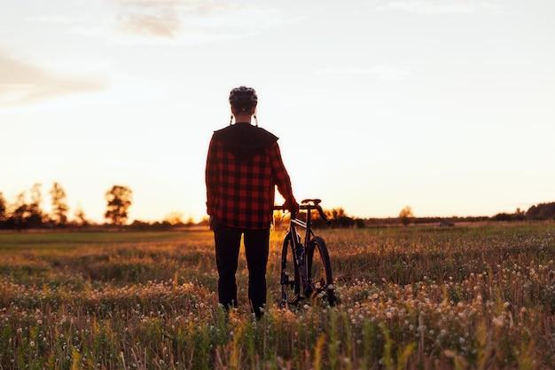 Silhouet van een fietser en zijn fiets tegen de achtergrond van de avondrood. healtht en sportief levensstijlconcept.