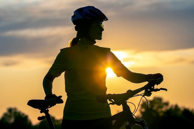 Silhouet van een fietser meisje met een fiets op de achtergrond van een avondrood. gezonde levensstijl en sport. vrije tijd en hobby's