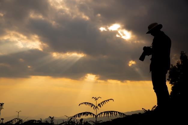 Silhouet van een fotograaf die een zonsondergang in de bergen schiet