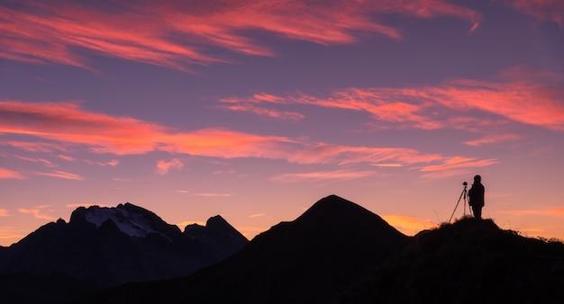 Silhouet van een fotograaf op de bergpiek tegen rotsen en paarse hemel met roze wolken bij zonsondergang