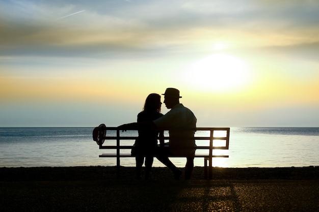 Silhouet van een gelukkig liefdevol paar bij zonsondergang aan de kust