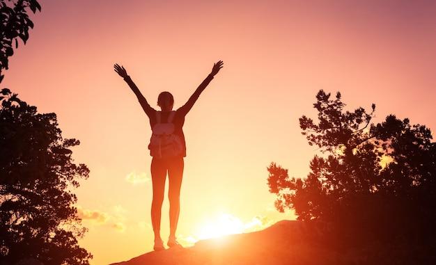 Silhouet van een gelukkige jonge vrouw in bergen bij zonsondergang