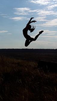 Silhouet van een gracieuze acrobatische vrouw die hoog in de lucht springt tegen een blauwe hemel in de late namiddag